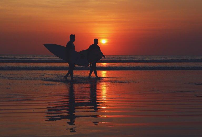 Dos surfistas paseando por la playa de Kuta con el amanecer de fondo